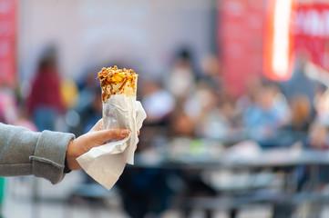 Female's hand in grey coat holding toner kebab or burrito on blurred festival background