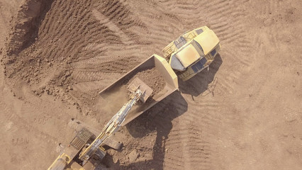 Large track hoe excavator filling a dump truck with rock and soil for fill at a new development construction project.