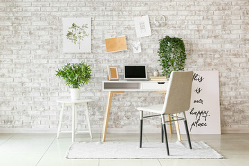 Comfortable workplace with mood board and laptop near brick wall