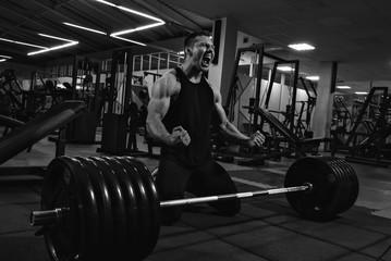 Young man powerlifter after deadlift
