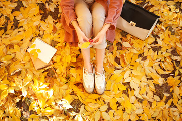 Beautiful young woman resting in autumn park