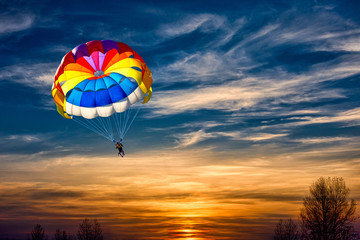 A man is gliding with a parachute on the background of sunset.