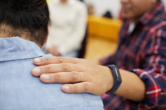 Closeup of young man crying in support group with psychologist comforting him, copy space