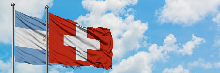 Argentina and Switzerland flag waving in the wind against white cloudy blue sky together. Diplomacy concept, international relations.