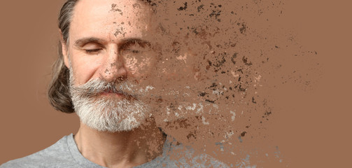 Crumbling mature man on color background. Process of aging