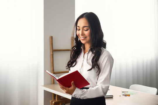 Beautiful Asian woman with book in office