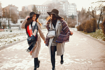 Fashionable girls in a winter city. Stylish ladies in a coats Wall mural