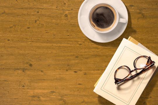 コーヒーと本のあるアンティークな木のテーブル