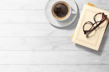 本とコーヒーのある白木のテーブル
