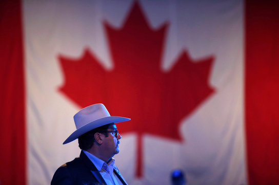 A man in a cowboy hat watches election results come in at Conservative leader Andrew Scheer's campaign headquarters during the federal election in Regina