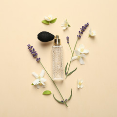 Flat lay composition with elegant perfume and beautiful flowers on beige background