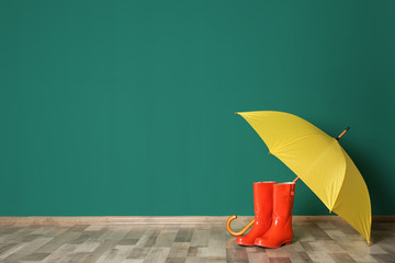 Wall Mural - Colorful umbrella and rubber boots on floor against green wall. Space for text