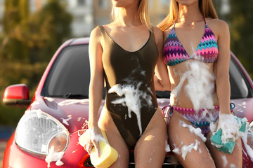 Young women in swimsuits with sponges near car outdoors, closeup Wall mural