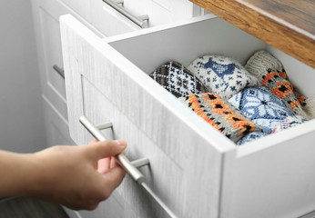 Fototapete - Woman opening drawer with warm socks indoors, closeup