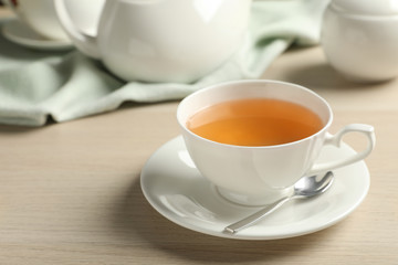 Cup of hot green tea on wooden table