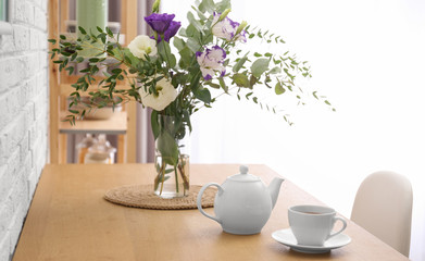 Teapot, cup and flowers on wooden dining table indoors. Kitchen interior