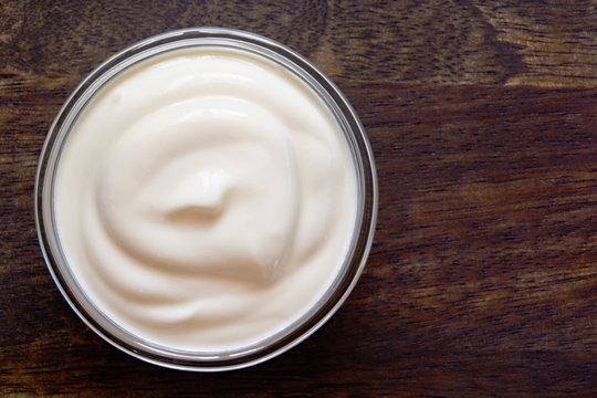 Yogurt, sour cream bowl on wood background. Healthy dairy food, white sauce portion