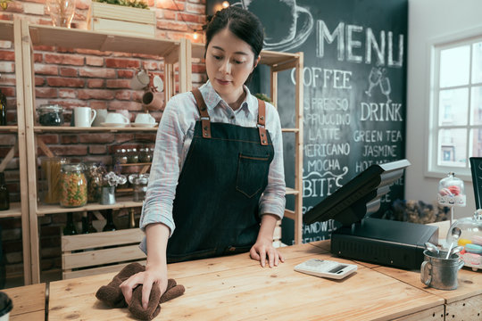 Young asian chinese woman waitress in apron thoughtfully wiping counter at workplace in restaurant. female barista in white shirt cleaning in bright modern coffee shop. girl staff working in cafe