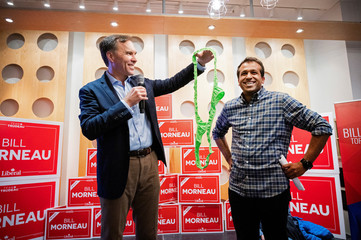 Bill Morneau, Canada's Finance Minister and Liberal Party candidate for Parliament, holds up a thong bathing suit to present to a campaign worker
