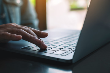 Closeup image of a woman typing and pressing finger on laptop computer keyboard