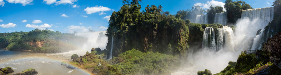 Aluminium Prints Dark grey A panoramic of the famous Iguazu Falls with many waterfalls gushing water on the a sunny day.