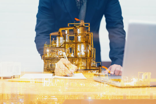 Double exposure of Engineering with oil refinery industry plant,engineer write industrial instruments plan in the factory and physical system with laptop, businessman Industry concept image