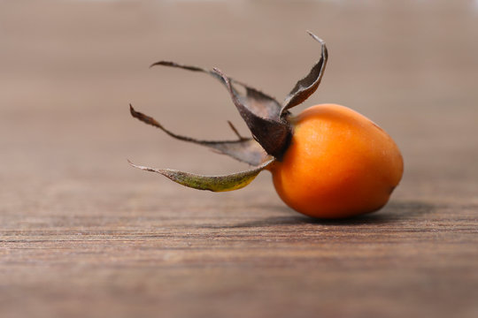 orange rose hip on a wooden background, herbal tea ingredient