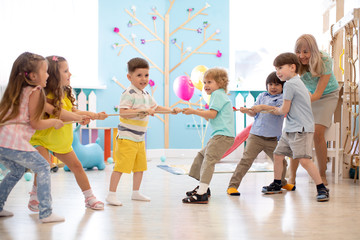 Group of children in a rope-pulling contest indoors