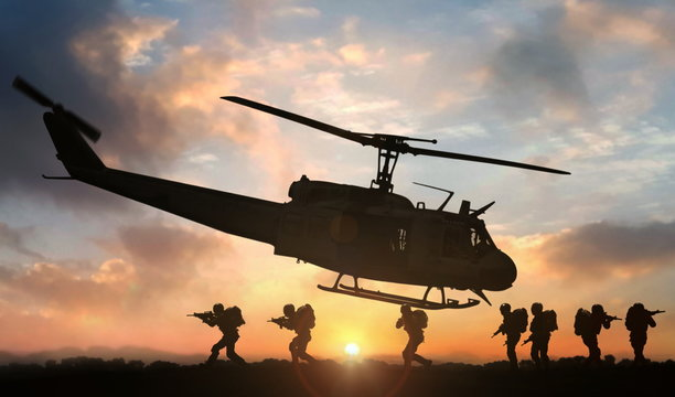 Military special force assault team helicopter drops during sunset