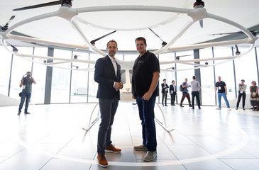 CEO Florian Reuter and co-founder Alexander Zosel of German startup Volocopter pose for a photo with a model of the Volocopter air taxi in Singapore