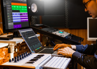 male producer, musician, composer making a song in home recording studio. music production concept