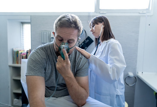 Sick man Inhaling Through Oxygen Mask having a medical exam by female doctor at hospital