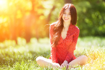 Foto auf Acrylglas Gelb Schwefelsäure Young cute woman in red dress relaxing in the park. Beauty nature scene with colorful background, trees at summer season. Outdoor lifestyle. Happy smiling woman sitting on green grass