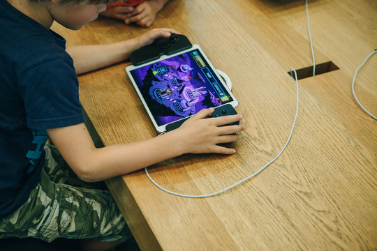 Berlin, August 29, 2018: A child plays an electronic game on an Apple game console or on an iPad with a special joystick that turns into a console.