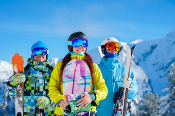 Happy man and woman with snowboard and skis standing on snow resort against backdrop of mountain in afternoon.