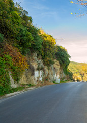 Asphalt road along mountain wall with green yellow bushes and leaves in bright day, Sariyer district, Bosphorus Strait, Istanbul, Turkey