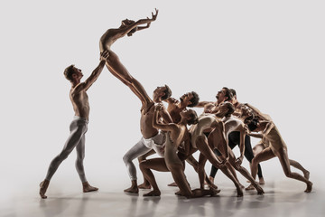 The group of modern ballet dancers. Contemporary art ballet. Young flexible athletic men and women...