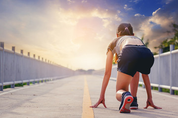 Woman runner getting ready to start running on the road with sunset background. summer outdoors training.