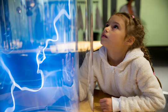 Finnish science center in Vantaa, Finland. Child studying electrical discharges in a lab.