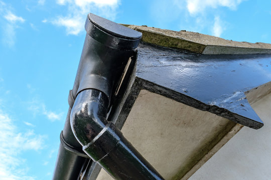 Detailed view of a detached house, showing detail of the guttering, roof line and down-pipe, against a clear sky in the autumn.