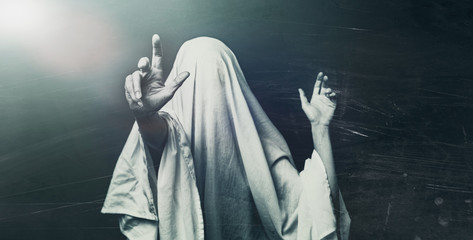Spooky white ghost on a gray background, black and white image. Halloween horror minimal concept