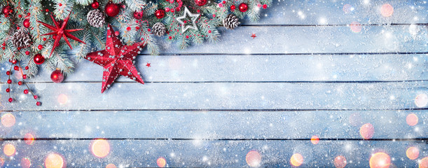 Fotomurales - Christmas Fir Branches On Wooden Blue Plank With Red Baubles And Snowfall