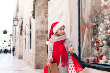 Christmas shopping. Child girl with paper bags on market street. Cute kid in red santa hat makes purchases by store showcase decorated with gifts, Christmas tree. Cozy fair, New Year and Black Friday