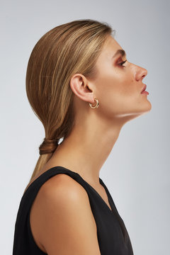 Cropped half-turn shot of a blond girl, posing on a grey background. She is wearing black tank top and golden open-ended round hoop earrings. Her hair pulled back in a ponytail.