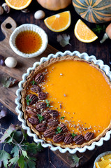 Pumpkin tart on a dark wooden background, still life