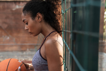 Image of african american woman playing basketball at playground