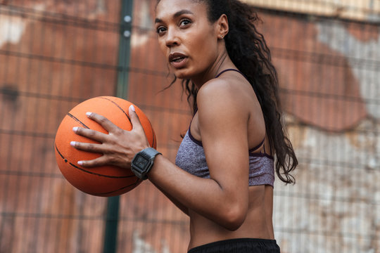 Image of african american woman playing basketball at playground outdoors