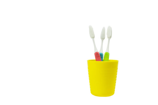 three toothbrush in yellow plastic glass isolated on a white background with clipping part.