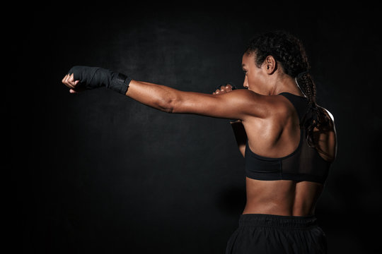 Image of muscular african american woman boxing in hand wraps