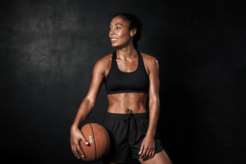 Image of smiling african american woman in sportswear holding basketball Fototapete